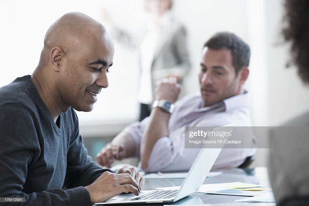 Businessman using laptop in meeting : Stock Photo