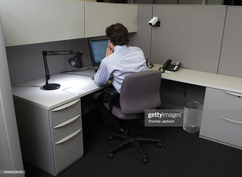 Businessman using laptop in office at desk, rear view : Stock Photo
