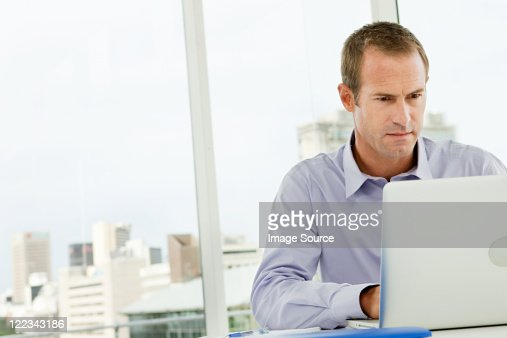 Businessman using laptop in office : Photo
