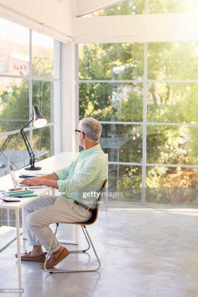 Businessman using laptop in office : Stock Photo