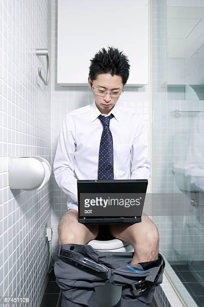 Businessman using laptop in restroom