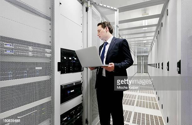 Businessman using laptop in server room