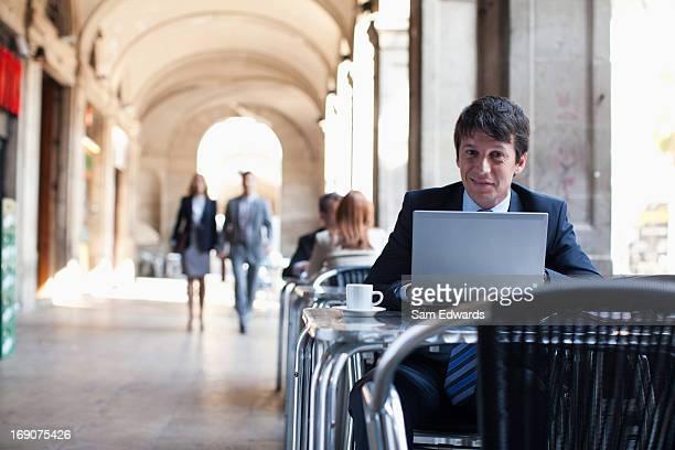Geschäftsmann mit laptop im Straßencafé