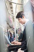 Businessman using laptop in Subway