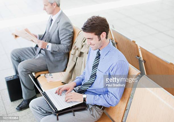 Businessman using laptop in train station waiting area
