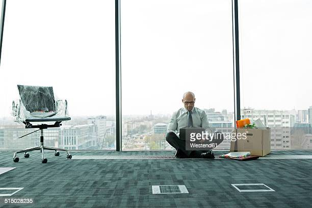 Businessman using laptop on empty office floor with cardboard box