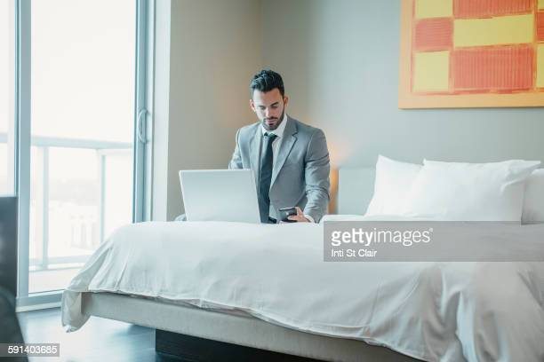 Businessman using laptop on hotel bed