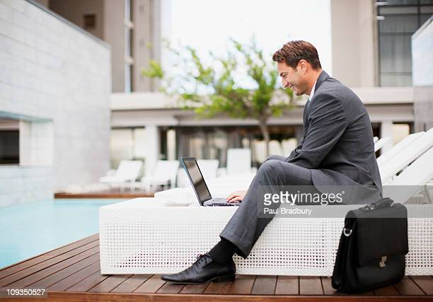 Businessman using laptop on lounge chair near swimming pool