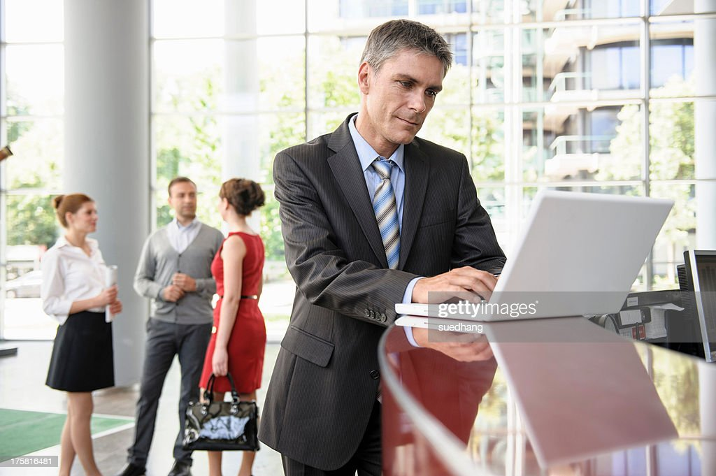 Businessman using laptop on reception desk : Stock Photo
