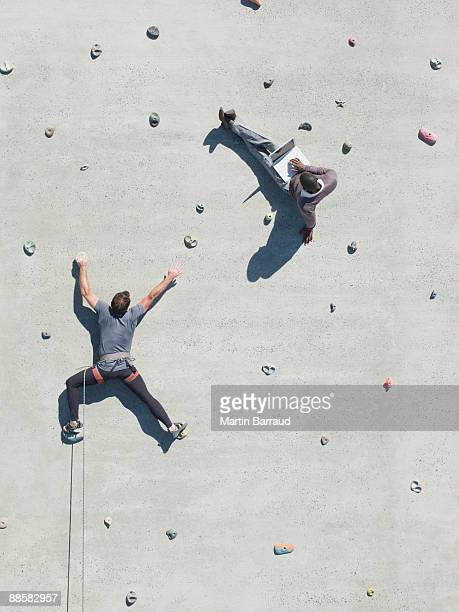 Businessman using laptop on rock climbing wall