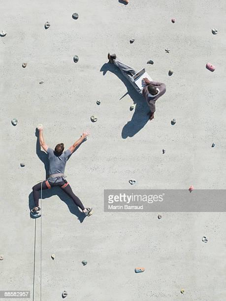 Businessman using laptop on rock climbing wall