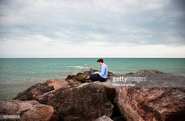 Businessman using laptop on rocks near ocean