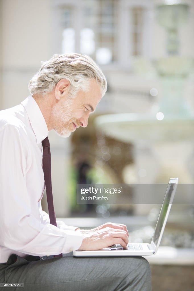 Businessman using laptop outdoors : Stock Photo
