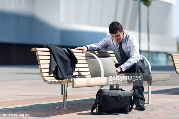 Businessman using laptop sitting on bench