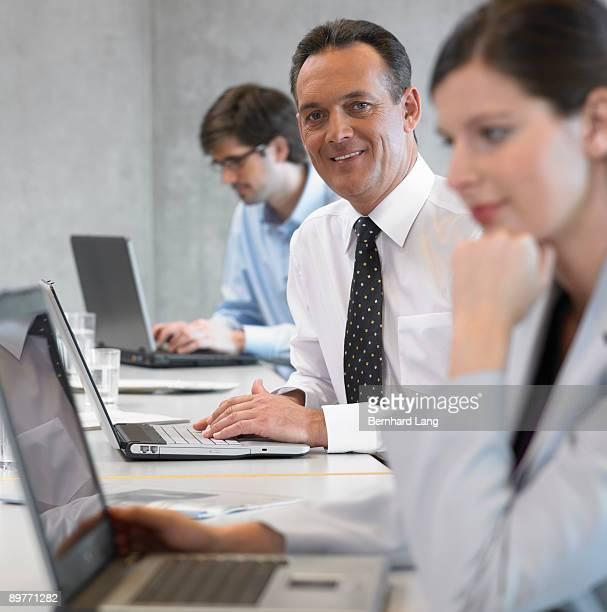 Businessman using laptop, smiling