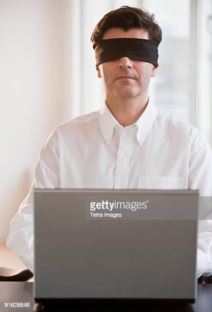 Businessman using laptop while blindfolded
