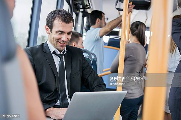 Businessman using laptop while commuting to work.