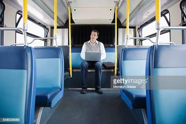 Businessman using laptop while riding public bus