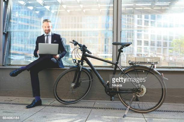 Businessman using laptop while sitting by bicycle against glass building