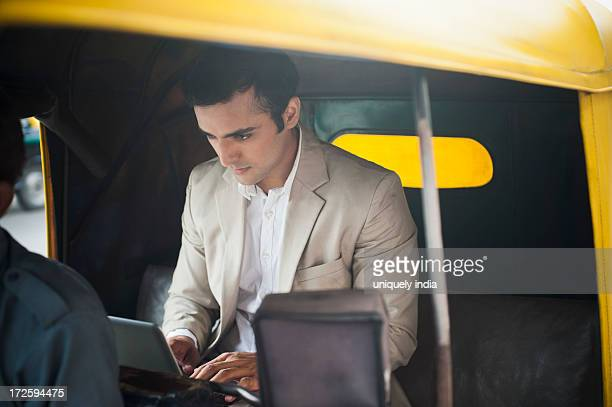 Businessman using laptop while traveling in an auto rickshaw