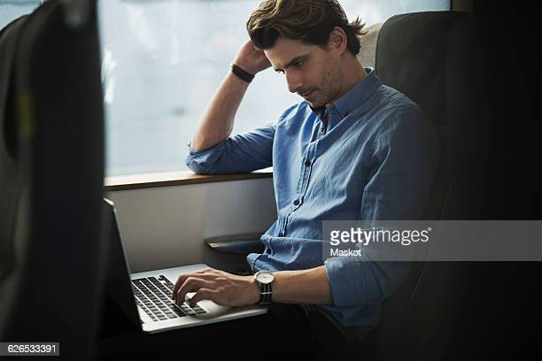 Businessman using laptop while traveling in train
