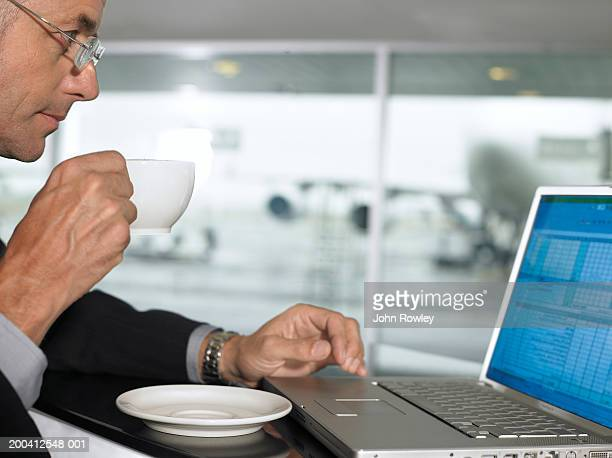 Businessman using laptop whilst drinking from cup, profile, close-up