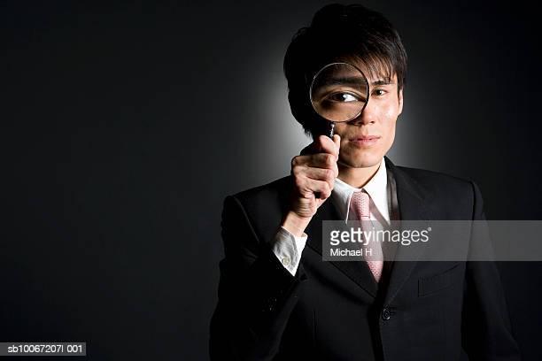 Businessman using magnifying glass, studio shot