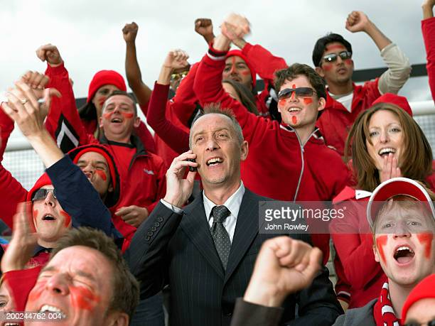 Businessman using mobile phone amongst cheering stadium crowd