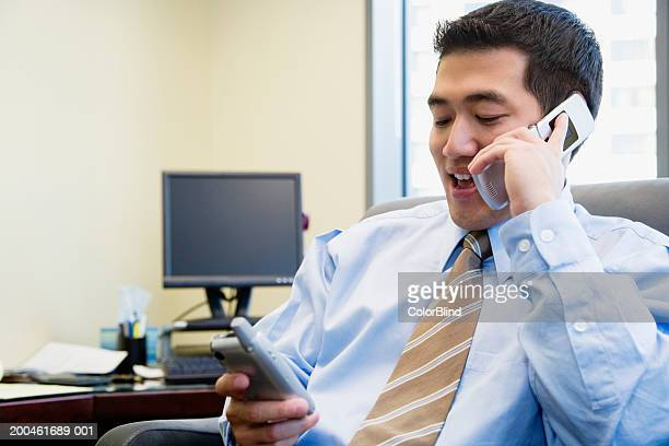 Businessman using mobile phone and looking at personal organizer