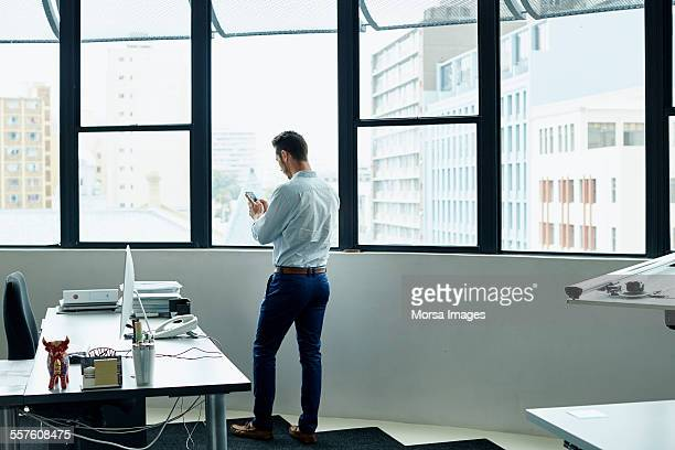 Businessman using mobile phone by office window