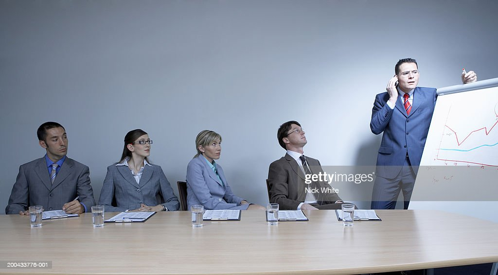 Businessman using mobile phone during presentation in boardroom : Stock Photo