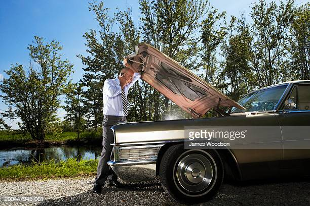 Businessman using mobile phone holding open car bonnet