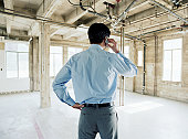 Businessman using mobile phone in empty office space, rear view