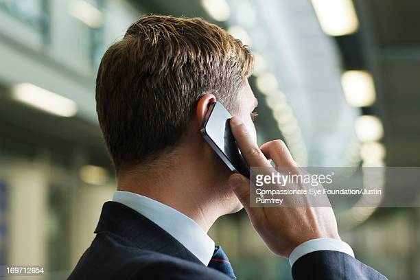Businessman using mobile phone in office hallway