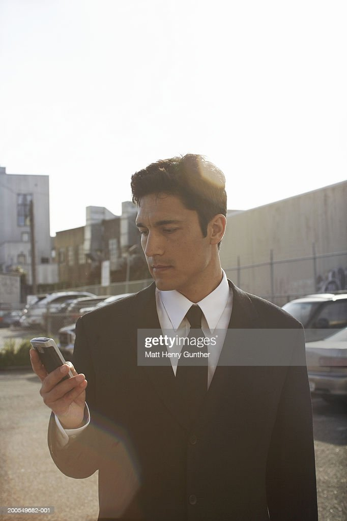 Businessman using mobile phone in parking lot : Stock Photo