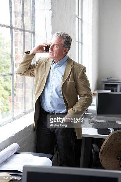 Businessman using mobile phone in window of office