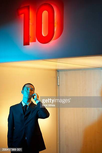 Businessman using mobile phone under neon '10' sign