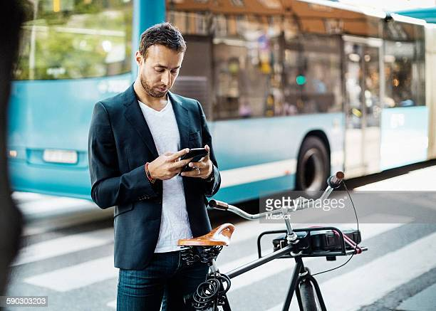 Businessman using mobile phone while standing with bicycle on city street