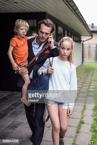 Businessman using mobile phone while walking with children at yard