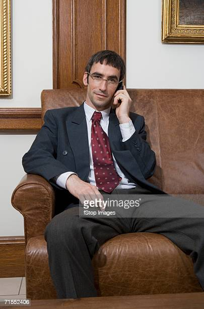 Businessman using mobile phone whilst sitting on leather sofa