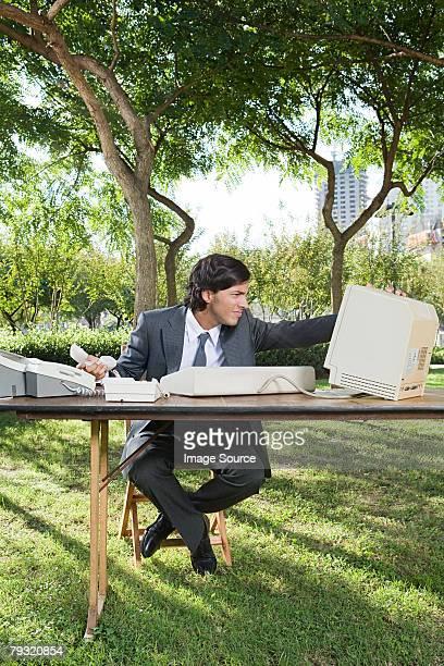 Homme d'affaires à l'aide d'ordinateur dans le parc