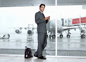 Businessman using palm top in airport, leaning against window