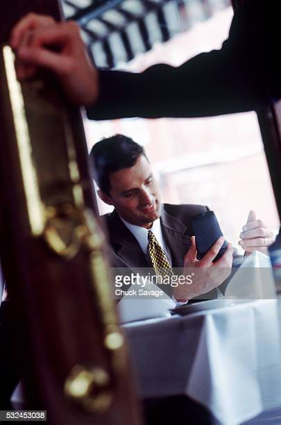Businessman using palmpilot in a restaurant