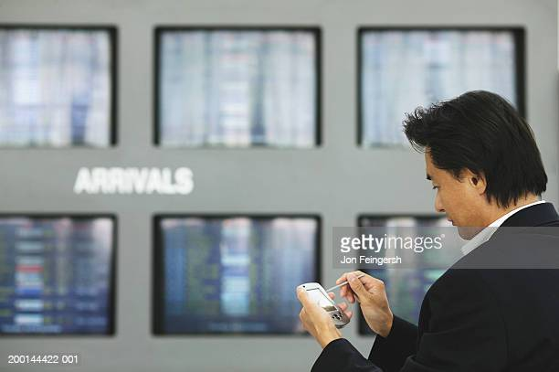 Businessman using palmtop in airport, side view