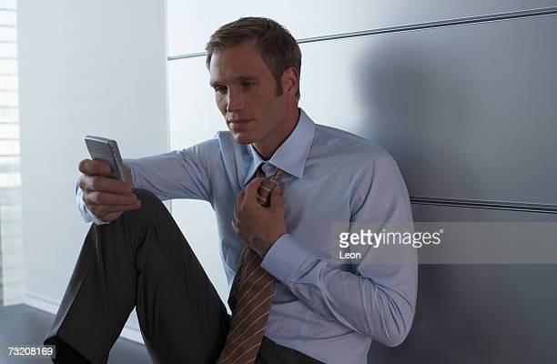 Businessman using palmtop on kitchen counter