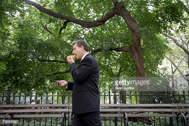 Businessman using PDA and eating hot dog while walking outdoors, side view