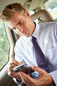 Businessman using PDA in car