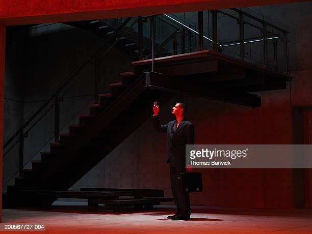 Businessman using PDA in stairwell, side view