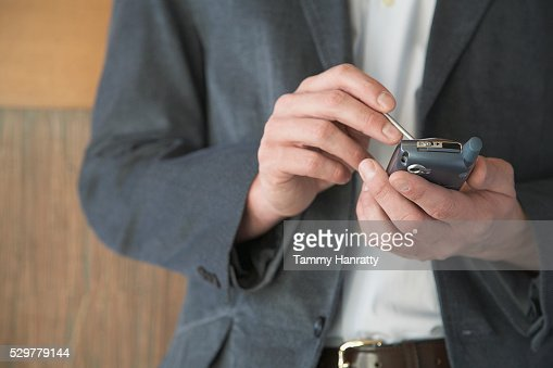 Businessman using personal digital assistant : Stock-Foto
