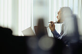 Businessman using phone in office, looking through window